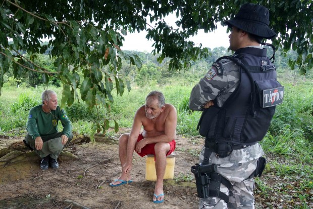 An officer of the Brazilian Institute of Environment and Renewable Natural Resources questions a man found living near a recent deforestation site.